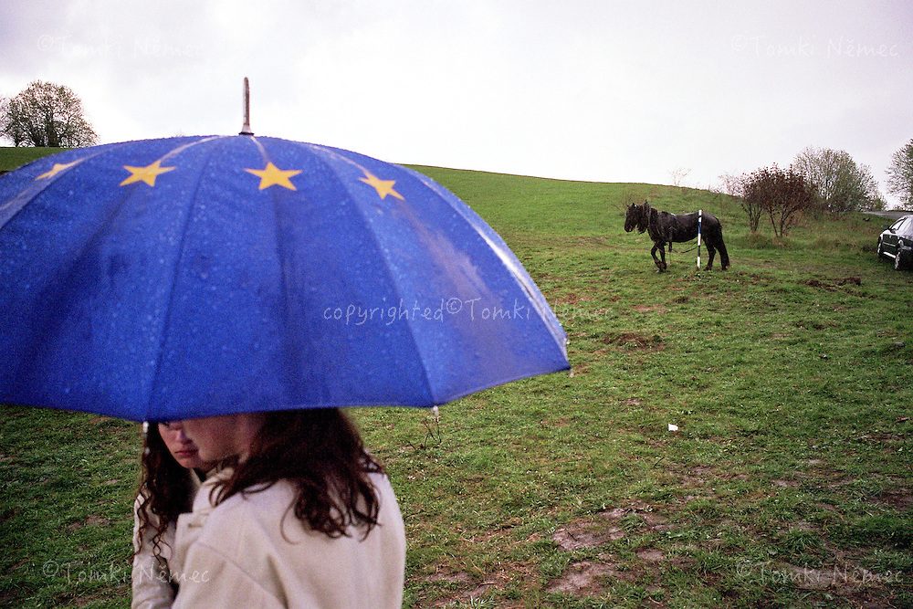 Two young girls in rain, at the geographical centre of Europe, near to Kremnicke Bane, at a party celebrating entry of Slovakia into EU, on May 1st 2004.