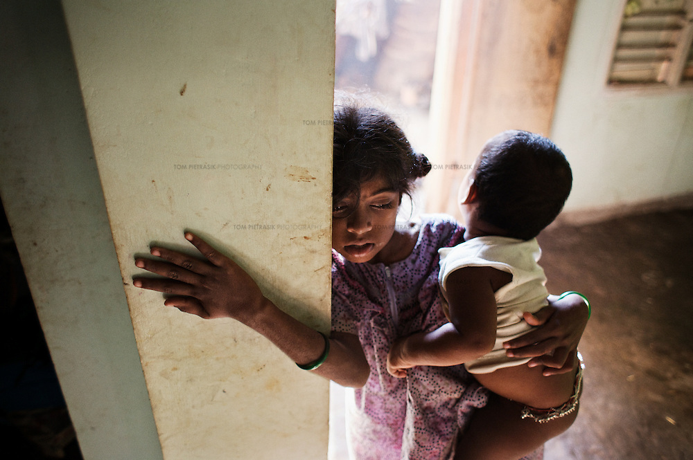 While her step-mother makes breakfast, Vijyashree Viswanathan cares for her brother at home in Thalanguda. Vijyashree lost her mother and first brother to the Tsunami. Since then her father has remarried and now has two children by his second wife.<br /> <br /> Vijitha and Vijyashree Viswanathan, now age 12 and 10, lost their mother and younger brother to the 2004 Asian Tsunami. The sisters continue to live with their father Viswanathan in a small house in the fishing village of Thalanguda, 5km from Cuddalore. The house does not have a toilet and water is supplied for only a short period of the day. Viswanathan married Kayalvizhi just over a year after the tsunami and the couple now have a son born in December 2006. Of the two sisters it was the elder Vijitha who initially appeared more distressed at her mother's death. But in the subsequent three years she has come to terms with her loss and seems better equipped to face the challenges of growing up without the support of her mother. In contrast Vijyashree, whos younger age may have insulated her from some of the grief experience by her sister, has fallen back in her studies becoming moody, withdrawn and reticent. Vijyashree has suffered fits for a number of years but in the past twelve months these have become more frequent. Viswanathan blames the drugs prescribed to treat his daughter's condition for her moodiness. Another explanation could be the arrival of Vijyashree's half-brother Sanjay with whom she must now compete for the affections of her father. Kayalvizhi does not appear particularly sensitive to the needs of her adopted daughters though her position cannot be easy, particularly when burdened with the task of raising a baby. Viswanathan's sister-in-law Shanthi is especially scathing of Kayalvizhi's indifference to Vijitha and Vijyashree and questions whether the girls should be expected to clean the house, clean utensils and prepare themselves for school. Shanthi complains that the girls must come to her for affect