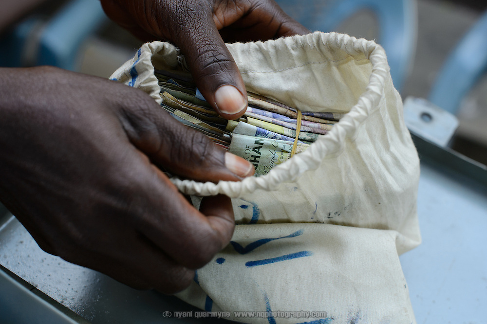 Patience Kortsu, an onion seller, secures her group's savings in a cash box at a 'Banking on Change' Village Savings and Loan Association (VSLA) meeting at Dabala Junction in the Volta Region of Ghana on 12 September 2012. Members contribute savings weekly and receive a payout commensurate with their inputs at the end of each year. Members may also access small loans, which many use to support entrepreneurial activities, and they make small insurance contributions which may be drawn upon in the event that an individual member has a financial emergency.