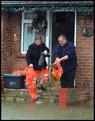 Residents empty flood water from their wellies as floods hit Egham, United Kingdom, Wednesday, 12th February 2014. Picture by Andrew Parsons / i-Images