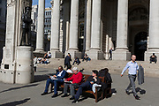 Londoners read their copies of newspapers below the classical architecture of Royal Exchange and the WW1 war memorial at Bank Triangle, on 10th May 2017, in the City of London, England.