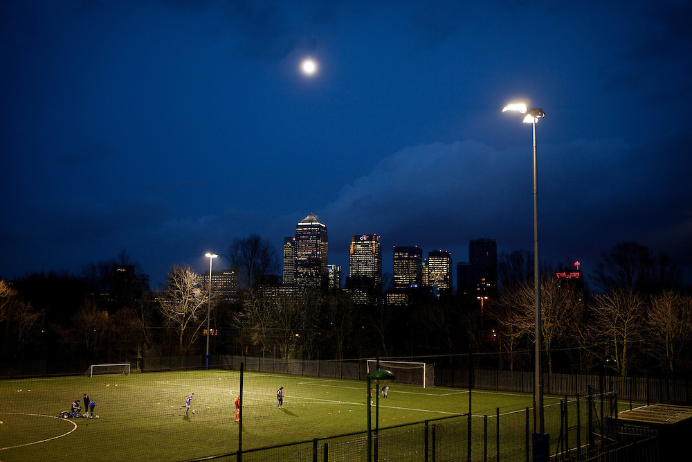 Kids play football at a school in South London with Canary Wharf in the background. London, Uk.