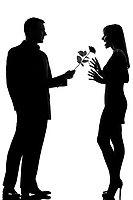 one caucasian lovers couple man offering rose flower and woman surprised in studio silhouette isolated on white background