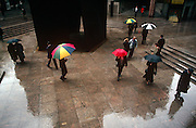 Londoners from a break from their office jobs, take a walk in the rain at Broadgate in the City of London, the capital's heart of its financial district. The reflection of an 80s steel art instillation and the surrounding corporate development is seen on the ground as we look down from a high vantage point. Coloured umbrellas look all the brighter in the subdued light and wet conditions. The people come and go in their 90s fashion. The art is called Fulcrum (1987) by Richard Serra, a sculpture commissioned for the west entrance to Liverpool Street station in the Broadgate complex.