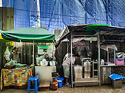 21 SEPTEMBER 2016 - BANGKOK, THAILAND: Food stalls on the outside of the construction site that used to be the Bang Chak Market. The market closed permanently on January 4, 2016. The Bang Chak Market served the community around Sois 91-97 on Sukhumvit Road in the Bangkok suburbs. Bangkok city authorities put up notices in late November 2015 that the market would be closed by January 1, 2016 and redevelopment would start shortly after that. Market vendors said condominiums are being built on the land.      PHOTO BY JACK KURTZ