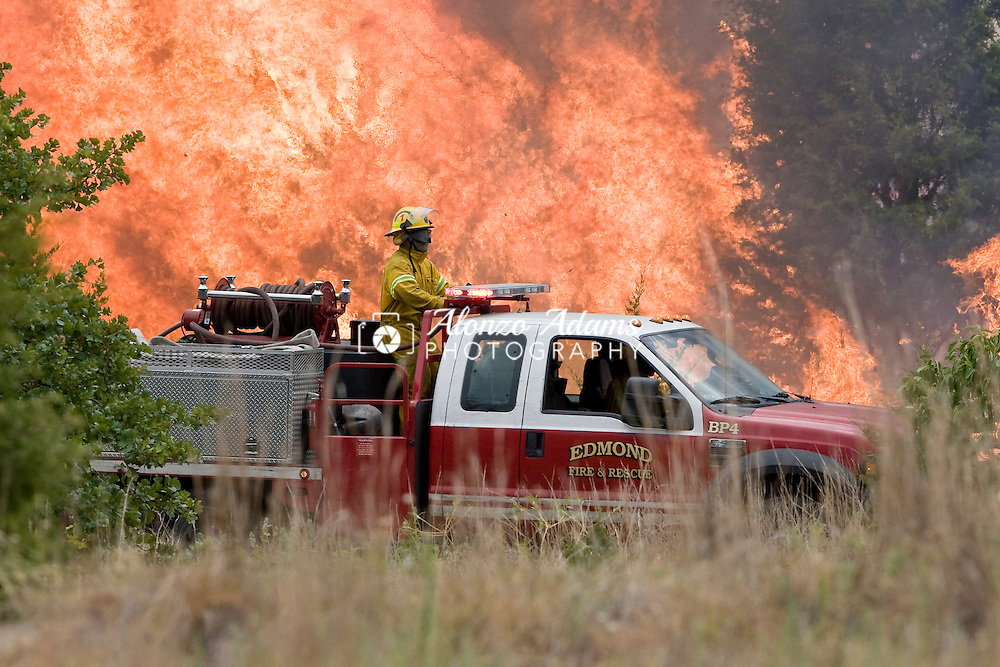 A wildfire burns out of control as Edmond Fire Crews try to contan it between Coffee Creek and Covell Road in Edmond, Okla. on Saturday, August 6, 2011.  (Photo copyright Alonzo J. Adams)