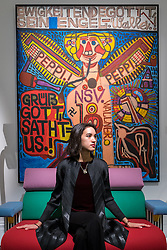 "© Licensed to London News Pictures. 01/11/2016. London, UK. A staff member sits in front of ""Ewigkeitendegottt, Sein Engel"" by August Walla, est. GBP6-8k. The first look of ""Bowie / Collector"", artworks from the late David Bowie's personal art collection, ahead of their sale later this month at Sotheby's. Photo credit : Stephen Chung/LNP"