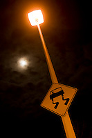 Light standard and slippery sign combine ominously with the moon behind a bank of clouds.