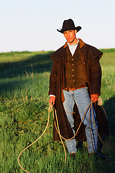 rugged cowboy holding a lasso on a ranch in New Mexico