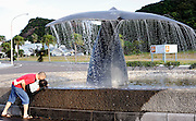 A man and his daughter play with the water from a fountain outside the whaling museum in Taiji, Japan on 10 September 2009..Photographer: Robert Gilhooly