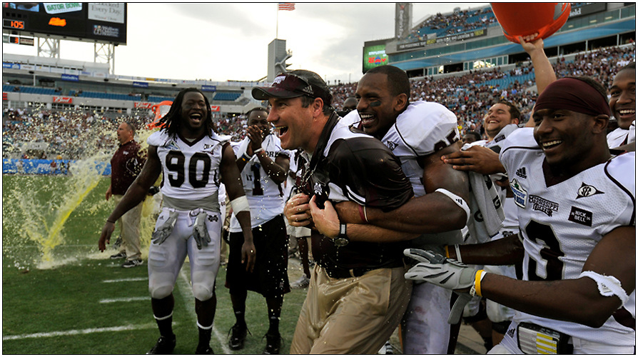 Mississippi State head coach Dan Mullen and his players celebrate on the sidelines in the final seconds during the second half of the Gator Bowl NCAA college football game against Michigan in Jacksonville, Fla., Saturday, Jan. 1, 2011. Mississippi State beat Michigan 52-14. (AP Photo/Stephen Morton)