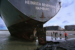 """BLANKENBERGE, BELGIUM - NOVEMBER 9, 2001 -  Workers from the salvage company Unie Van Redding - En Sleepdienst N.V. survey the damage to the German cargo ship """"Heinrich Behrmann"""", which was beached by heavy seas after losing power to the main engine late Thursday night at Blankenberge. The ship was heading for the port at Zeebrugge from Ireland, and was carrying dry cargo, none of which was hazardous. Unie Van Redding - En Sleepdienst N.V. was hired to free the ship. Three unsuccessful attempts were made Friday, the second attempt resulted in the injury of two workers when tug boat cables snapped. The beached ship has attracted the attention of curious tourists. (Photo © Jock Fistick)"""