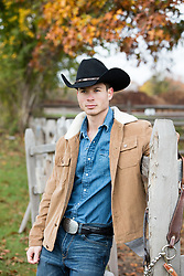 cowboy by a wooden fence on a ranch