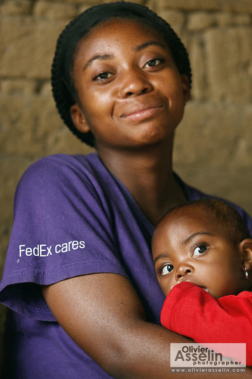 A woman holds her daughter as they wait at the Kasambondo health center in the village of Kasambondo, Katanga province, Democratic Republic of Congo on Sunday February 19, 2012..