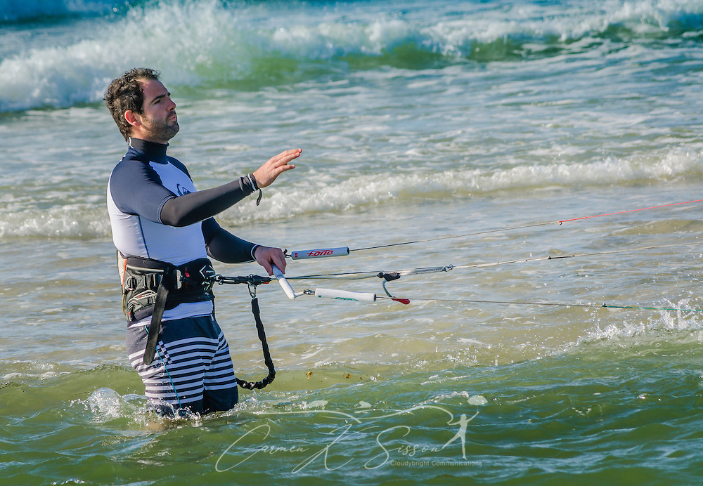 Mathieu Junco looks toward his assistant onshore as he gives the signal to launch his F-One Bandit Six kite, October 18, 2015, in Dauphin Island, Alabama. Junco, from France, began kitesurfing five years ago. Windy conditions on the island brought surfers out in droves, but many, like Junco, found that the brisk northerly winds made kitesurfing challenging on the south side of the island. Kitesurfing began in France in the 1980's and became a mainstream water sport in 1999, combining aspects of wakeboarding, windsurfing, surfing, and paragliding. More than 1.5 million people participate in the global sport. (Photo by Carmen K. Sisson/Cloudybright)