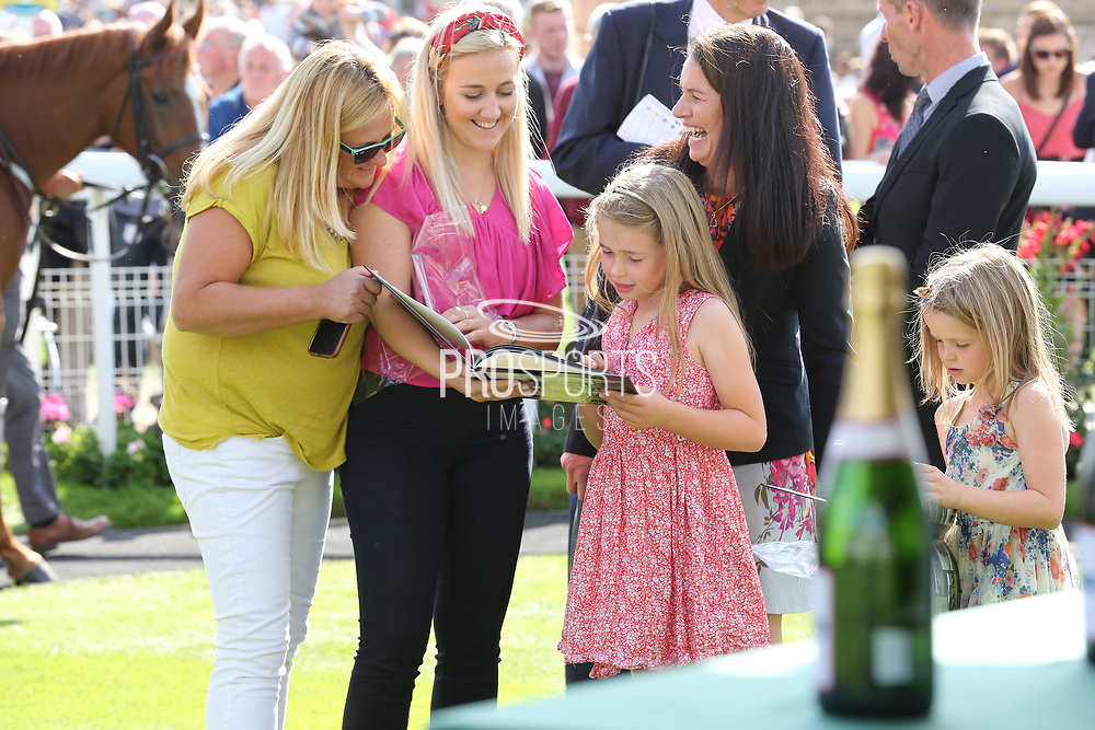 The Macmillan Riders families looking through the books that were presented to the Macmillan Riders during the Family Race Day held at York Racecourse, York, United Kingdom on 8 September 2019.