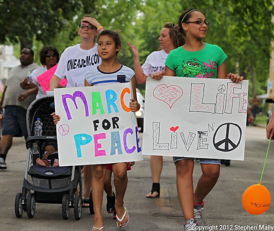 "Tay Jennings (from left), 9, and Kaeniece Lanier, 12, both of Cedar Rapids, hold up signs during a ""Stop the Violence March"" in Cedar Rapids on Saturday afternoon, May 19, 2012. The march was organized by a group of people fed up with the recent violence. About 90 people participated in the march with many people joining along the way. They plan on organizing a march monthly in various parts of town where there has been recent violence. (Stephen Mally/Freelance)"