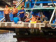 01 OCTOBER 2015 - MAHACHAI, SAMUT SAKHON, THAILAND: Fishing crewmen on the back of a Thai fishing trawler in Mahachai, one of Thailand's largest fishing ports. Thailand's fishing industry had been facing an October deadline from the European Union to address issues related to overfishing and labor practices. Failure to adequately address the issues could have resulted in a ban on Thai exports to the EU. In September Thai officials announced that they had secured an extension of the deadline. Officials did not say how much extra time they had to meet the EU goals. Thailand's overall annual exports to the EU are between 23.2 billion Thai Baht and 30 billion Thai Baht (US$645 million to US $841 million). Thailand's total fish exports were worth about 110 billion baht in 2014.    PHOTO BY JACK KURTZ