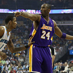 April 24, 2011; New Orleans, LA, USA; Los Angeles Lakers shooting guard Kobe Bryant (24) is guarded by New Orleans Hornets small forward Trevor Ariza (1) during the first quarter in game four of the first round of the 2011 NBA playoffs at the New Orleans Arena.    Mandatory Credit: Derick E. Hingle