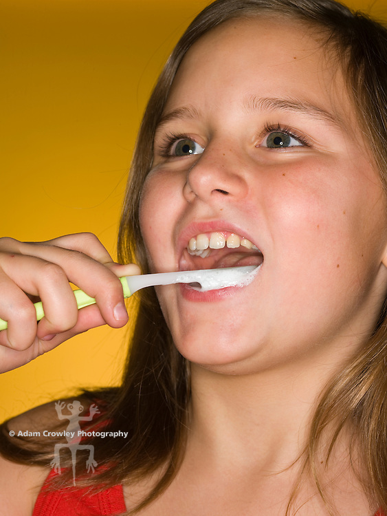Girl (10 years old) brushes her teeth with toothbrush and toothpaste, close up.