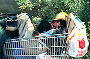 Homeless man age 35 sleeping in cart at Fisherman's Wharf.  San Francisco  California USA