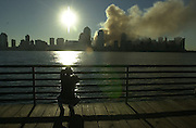 A man kneels in silence as the  sun rises over the skyline of New York City on 09/12/01, the morning after a  terrorist attack destoyed the World Trade Towers.
