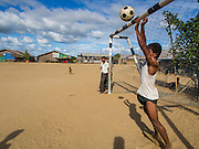 06 NOVEMBER 2014 - SITTWE, RAKHINE, MYANMAR: Residents of a Rohingya Muslim IDP camp watch some of the kids in the camp play soccer on a dirt pitch in the center of the camp. After sectarian violence devastated Rohingya communities and left hundreds of Rohingya dead in 2012, the government of Myanmar forced more than 140,000 Rohingya Muslims who used to live in and around Sittwe, Myanmar, into squalid Internal Displaced Persons camps.The government says the Rohingya are not Burmese citizens, that they are illegal immigrants from Bangladesh. The Bangladesh government says the Rohingya are Burmese and the Rohingya insist that they have lived in Burma for generations.  The camps are about 20 minutes from Sittwe but the Rohingya who live in the camps are not allowed to leave without government permission. They are not allowed to work outside the camps, they are not allowed to go to Sittwe to use the hospital, go to school or do business. The camps have no electricity. Water is delivered through community wells. There are small schools funded by NOGs in the camps and a few private clinics but medical care is costly and not reliable.   PHOTO BY JACK KURTZ