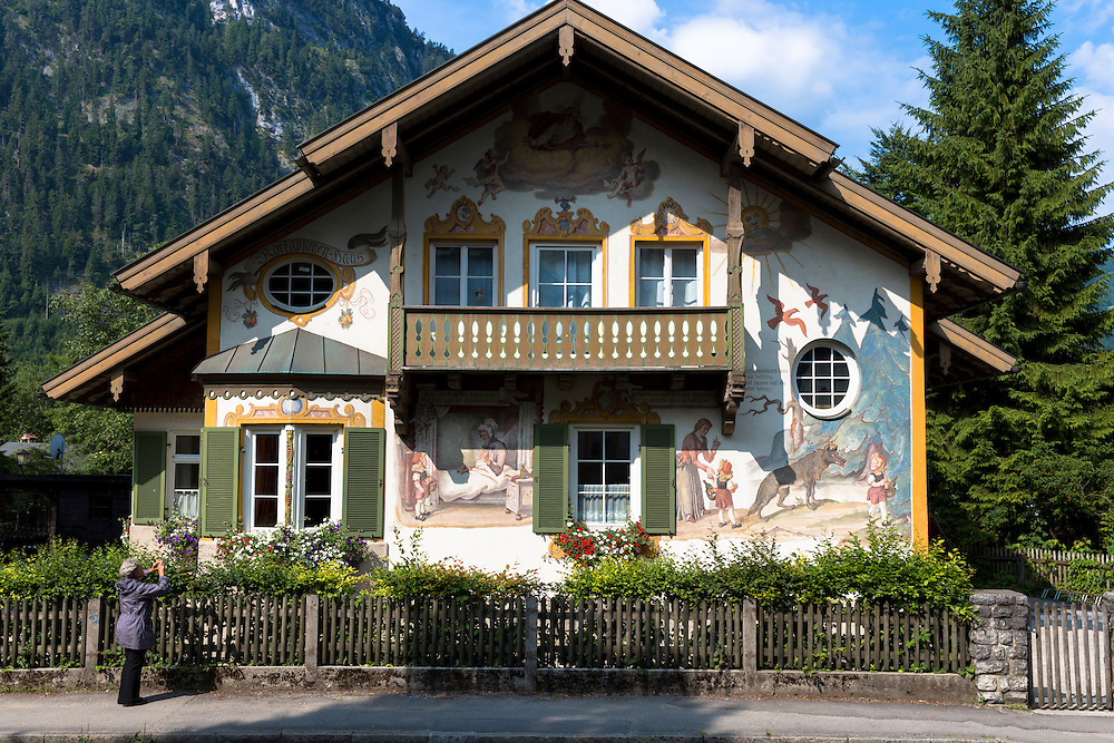 Tourist photographs painted facade of Grimms Fairy Tale Little Red Riding Hood in Oberammergau in Bavaria, Germany