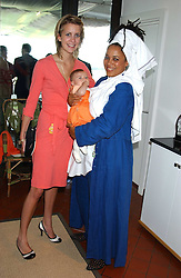 Left to right, LADY CANDIDA BALFOUR and NIMMY BURKE, she is actress Nimmy March adopted daughter of the Duke of Richmond holding her daughter LOTTI BURKE at the 4th day of the 2005 Glorious Goodwood horseracing festival at Goodwood Racecourse, West Sussex on 29th July 2005.    <br />