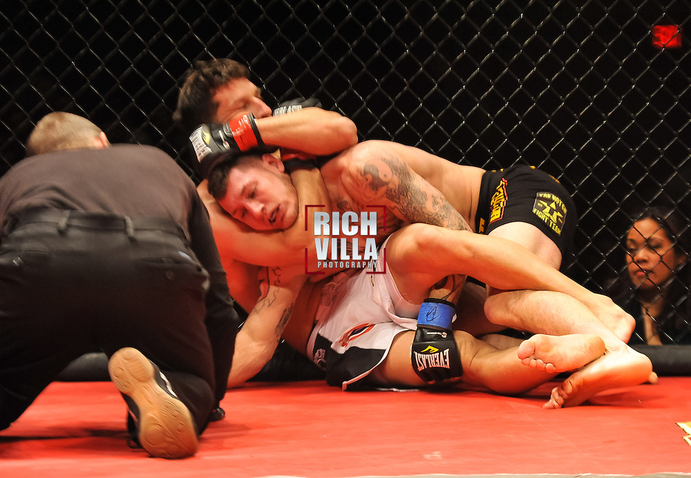 Atlantic City, New Jersey, January 24, 2014: Frankie Perez(far) chokes Mike Santiago(center) causing him to tap at Ring of Combat 47 at The Tropicana Casino.