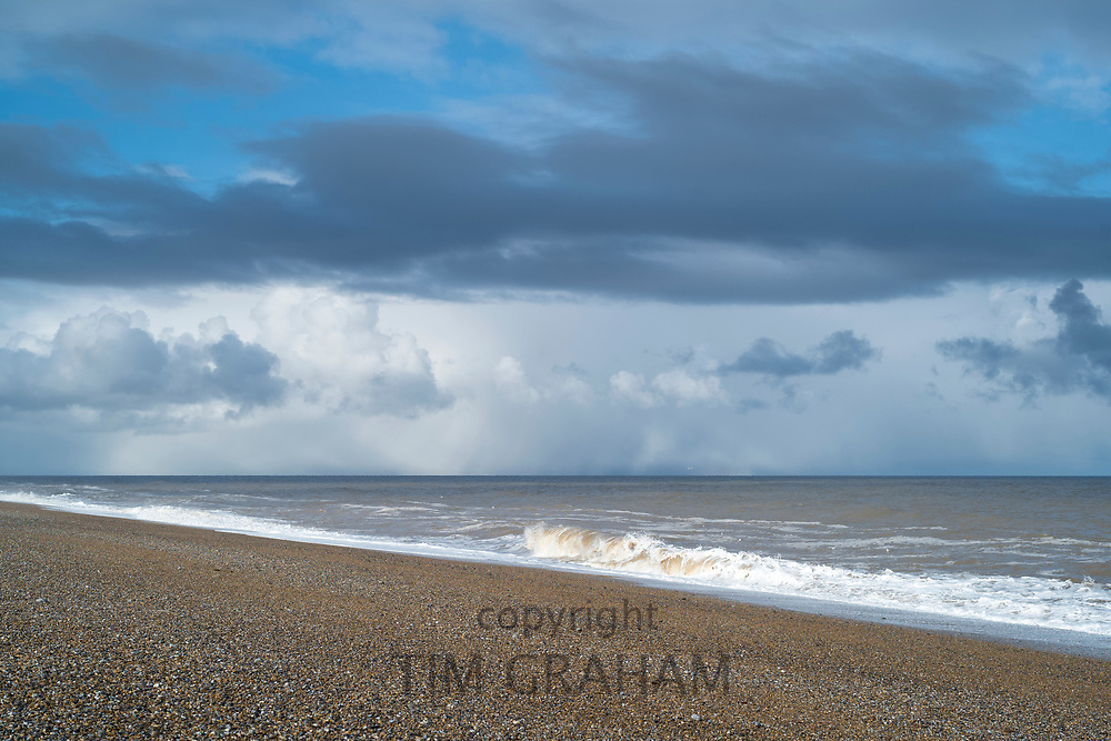 Shoreline and shingle pebble beach with blue sky and puffy dark clouds in wintertime at Cley Next The Sea, Norfolk, UK