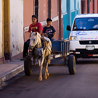 A vehicle with an impatient driver is delayed behind a horse and cart in the narrow streets of Granada, Nicaragua.