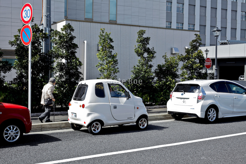 senior woman walking past a parked small single person disability vehicle Japan