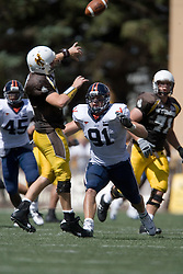 Pressure from Virginia defensive end Chris Long (91) forces Wyoming quarterback Karsten Sween (16) to intentionally ground the ball.  The Wyoming Cowboys defeated the Virginia Cavaliers 23-3 at War Memorial Stadium in Laramie, WY on September 1, 2007.