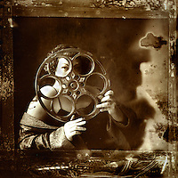 Sepia image of a young woman dressed in underwear and silk dressing gown looking through an old film reel,