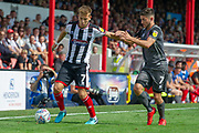 Grimsby Town midfielder Jake Hessenthaler holds back Lincoln City midfielder Tom Pett during the EFL Sky Bet League 2 match between Grimsby Town FC and Lincoln City at Blundell Park, Grimsby, United Kingdom on 18 August 2018.