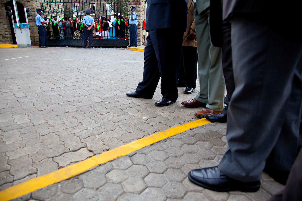Male parliament staffers watch as women's rights activists swarm the Kenyan Parliament in Nairobi, Kenya.