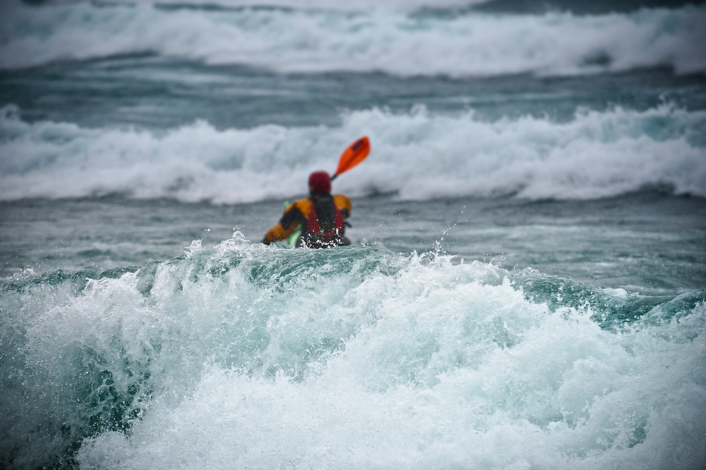 A sea kayaker in rough water storm conditions on Lake Superior in Ontario Canada.