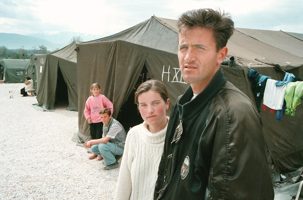 Nepresteno Refugee Camp. April 13, 1999. Three miles from Tetovo, north-west Macedonia. Four siblings of the Rrahmani family whose parents and elder sister are trapped behind in Kosovo. They do not know the fate of their parents (father Kadri, 59, and mother Nezire, 50) or sister (Hatixhe, 36). Siblings are: Mehmet, 28 (white shirt & dark jacket); Dashurije, 21 (white sweater); Hysen, 14 (stripped shirt & cut-off jacket); Sevdije, 10 (pink top). They are from the southern Kosovar village of Kashtanjeva. As the eldest son Mehmet has now taken on the role of father until they are reunited with their parents. They fled Kosovo over a mountain pass in yard-deep snow. Of a party of 30 villages, 10 became lost in driving sleet. Their fate is unknown although they are feared dead. One woman and someone's small daughter perished in the pass.