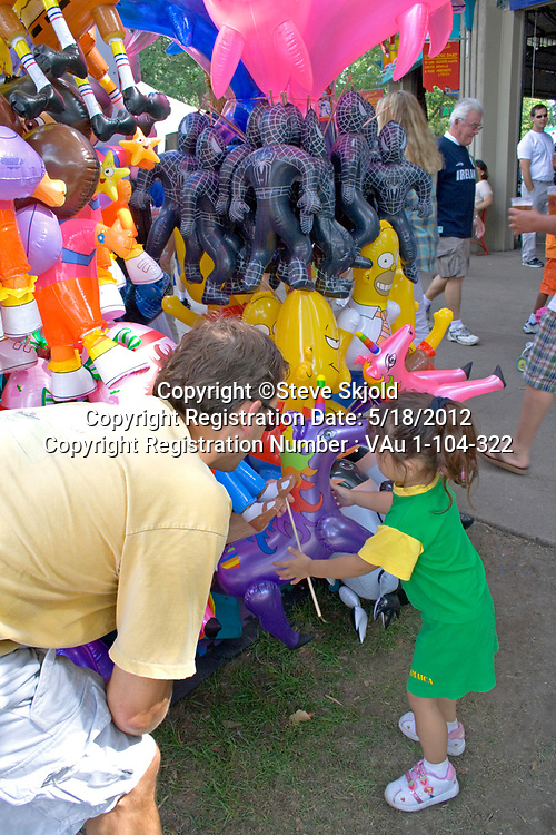 Dad helps daughter choose purple unicorn from balloon souvenir stand. Minnesota State Fair St Paul Minnesota MN USA
