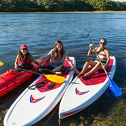 Women stand up paddleboarding and kayaking on the Essex River at the Cox Reservation in Essex, Massachusetts.