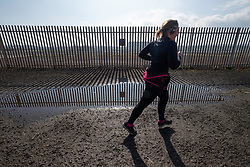 "Cockenzie, UK. 14 April, 2018. Jogger runs past site of the former Cockenzie power station in East Lothian, Scotland. A row has begun over concerns about the Scottish government's decision to ""call in"" a planning application by Red Rock Power to build a renewable energy sub-station on the site. Red Rock Power, part of China's largest state-owned investment fund, the State Development and Investment Corporation (SDIC), wants the the sub-station to allow it  to feed power from the Inch Cape offshore wind farm, near Angus, into the national grid."