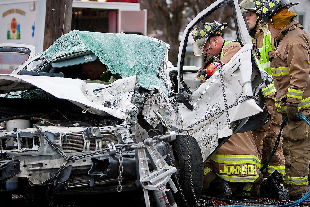 JEROME A. POLLOS/Press..Kootenai County firefighters work on extricating an accident victim from his Ford Countour sedan Friday following a head-on collision with a Jeep Cherokee at the intersection of Henry Street and Mullan Avenue. Three people were transported to Kootenai Medical Center with serious injuries after rescues crews worked for nearly a half hour to remove them from the vehicles.