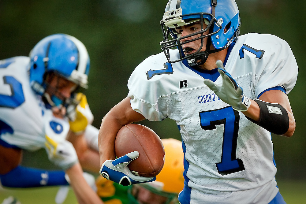 JEROME A. POLLOS/Press..Coeur d'Alene High's Cade Mendoza turns to run upfield after the catch as his teammate knocks down a chasing Lakeland defender during the first half of Friday's game.
