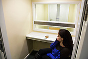 A prisoners wife waits to see her husband. Closed visits take place in locked rooms with a toughened glass window between the prisoner and his visitor.  HMP/YOI Portland, Dorset. A resettlement prison with a capacity for 530 prisoners. <br /> © prisonimage.org.  Any image use must be agreed first. All images must be properly credited.