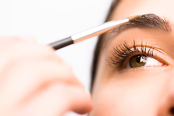 Extreme close up of a woman applying make up on her eyebrow