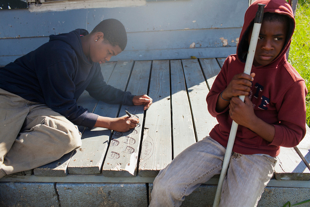 """Lakenson """"Duke"""" Bridges, 13, draws R.I.P. tombstones on the porch of an abandoned house while sitting next to his brother, Quarion Bridges, 10, in the Baptist Town neighborhood of Greenwood, Mississippi on October 17, 2013."""