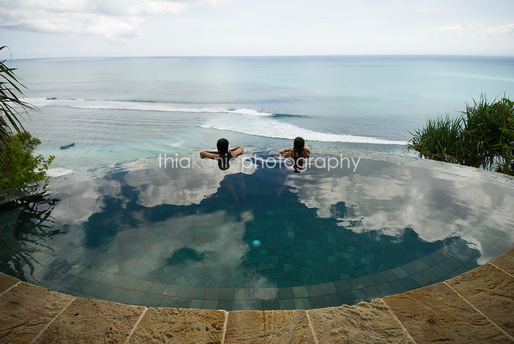 Two women peer over the rim of an infinity pool perched on the edge of a cliff over the ocean, Bali.