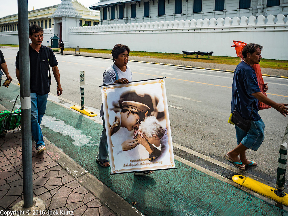 29 OCTOBER 2016 - BANGKOK, THAILAND: A man carries a photo of the late Bhumibol Adulyadej, the King of Thailand in front of the Grand Palace. Saturday was the first day Thais could pay homage to the funeral urn of the late Bhumibol Adulyadej, King of Thailand, at Dusit Maha Prasart Throne Hall in the Grand Palace. The Palace said 10,000 people per day would be issued free tickerts to enter the Throne Hall but by late Saturday morning more than 100,000 people were in line and the palace scrapped plans to require mourners to get the free tickets. Traditionally, Thai Kings lay in state in their urns, but King Bhumibol Adulyadej is breaking with tradition. His urn reportedly contains some of his hair, but the King is in a coffin,  not in the urn. The laying in state will continue until at least January 2017 but may be extended.       PHOTO BY JACK KURTZ