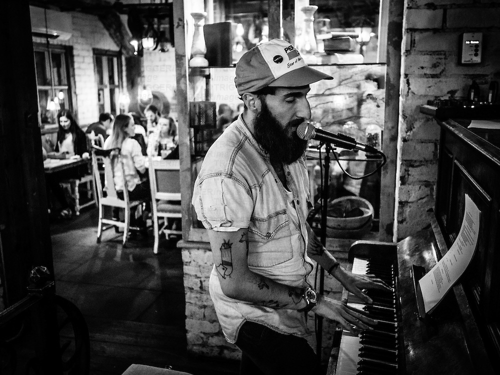 Male singer playing piano in bar